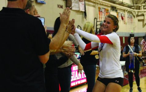 Senior Elly Lundberg high fives her coaches and teammates after winning NCS