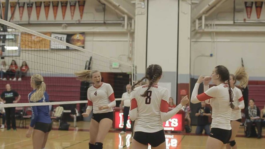 The girls' varsity volleyball starters celebrate winning a point in their game on Sept. 13