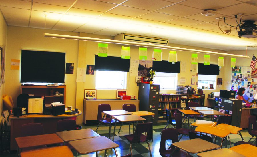 SITTING IN THE back of the room, Kemp works in a vacant classroom she shares stretching both facilities and teachers' with Social Studies teacher Nikolai Butkevich.