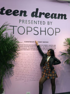 JUNIOR DANA NGUYEN poses in font of the sign for Teen Dream, an art exhibition in New York City.