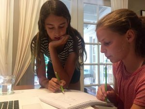 Helping a student through her math homework, a tutor provides an extra layer of support in the student's understanding of the concept.