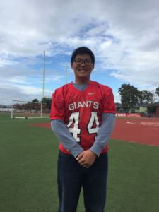 Sophomore Ethan Kim stands on the Redwood Football field, posing with his jersey.