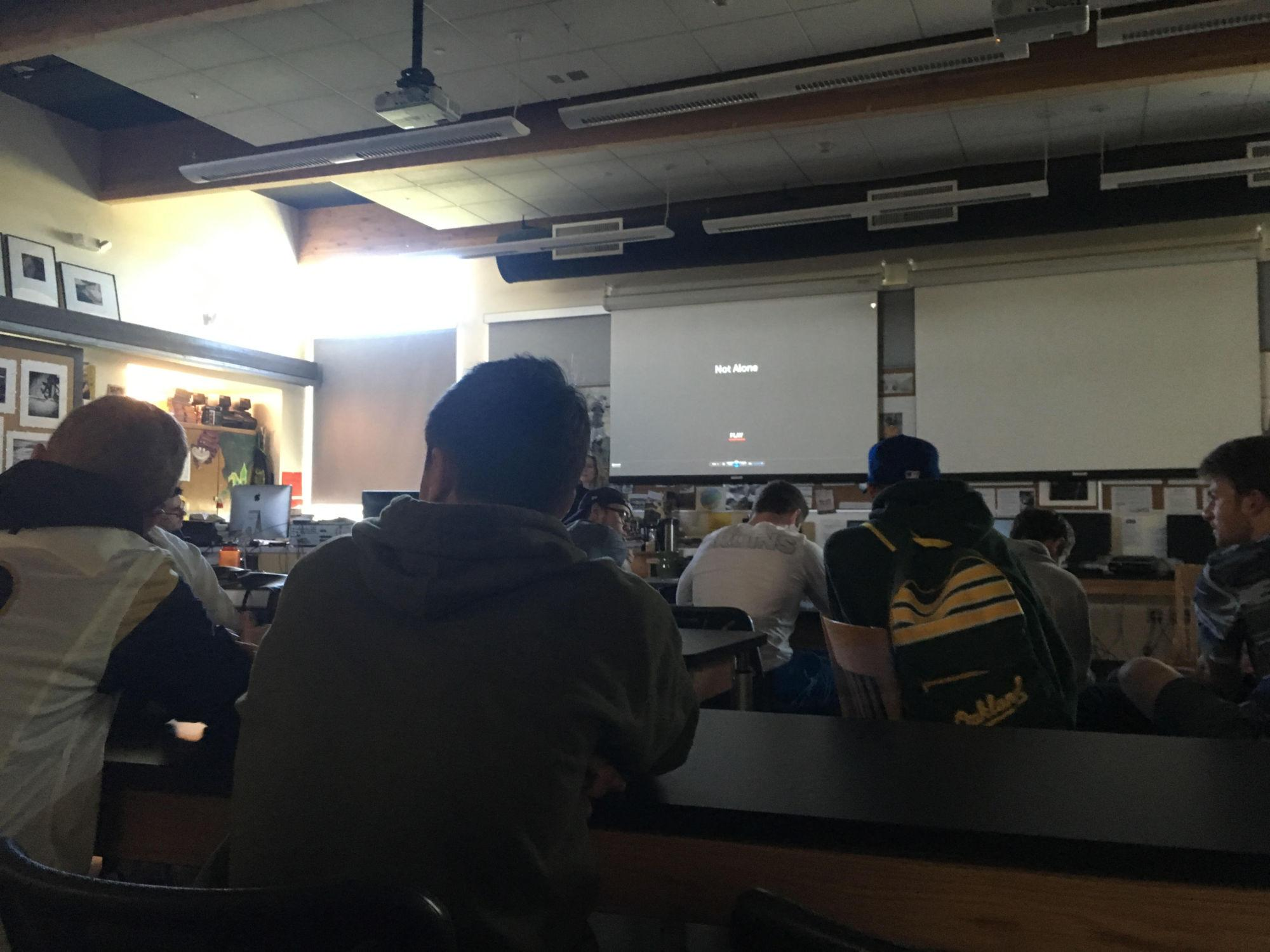 Students watch the screening of Not Alone in the Photo classroom