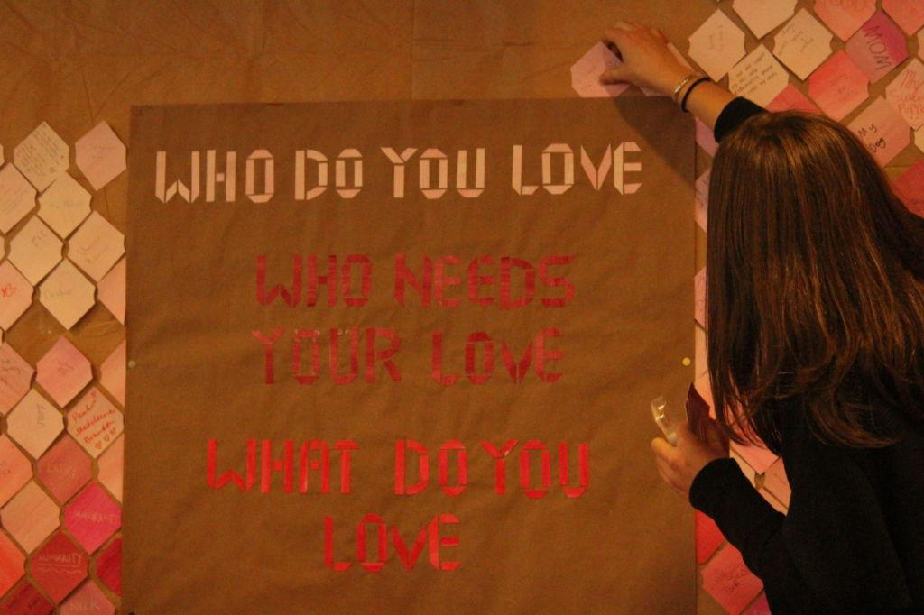 Senior art student Danielle Kisseberth places a tile on the CEA wall