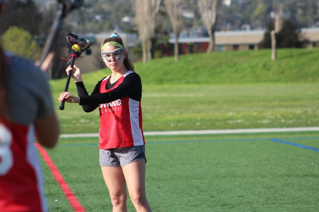 Training during an early season practice, sophomore Rachel Cramer plays catch with a teammate.