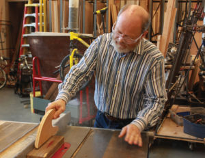 Demonstrating how to operate a saw in the shop, Esteb considers himself an artist, designer, architect, and builder.