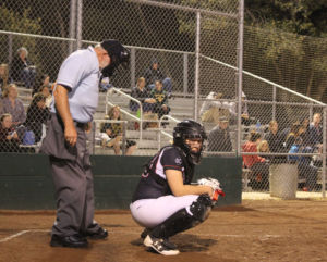 Attentively calling pitches, junior Mandy Weitenhagen takes a quick look to the dugout.