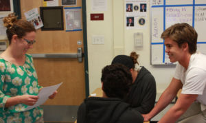 Working with her Government students, Ms. Kornfeld circulates the classroom to check in with table groups.