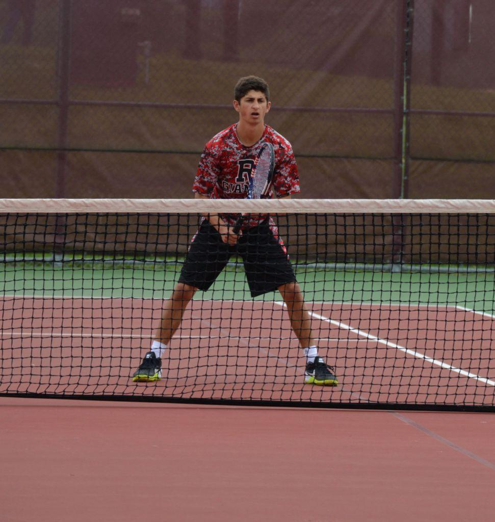 Senior Zach Babikian peers over the net during the team's playoff matchup against Branson.