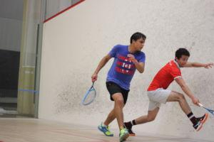 ESTÁ ALCANZANDO POR una corta pelota, Sergio Martin, un estudiante de ultimo año, corre a la pared de la cancha de squash cuando Cesar Segundo, un estudiante de tercer año, esprinta detrás de Martin para golpear la próximo pelota.