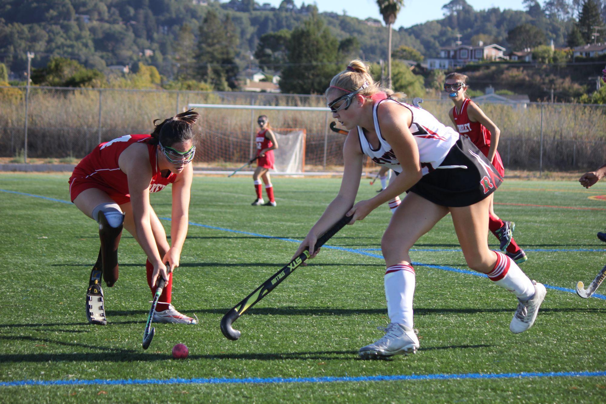 Defending the field, junior Caroline Soja runs towards the ball.