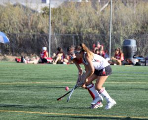 Fighting for the ball, junior Erin McCarthy crosses sticks with a defender.