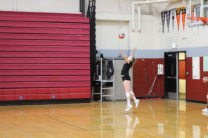 Serving the ball, volleyball player jumps high in the air.