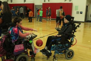 Dribbling the ball, students practice their basketball skills