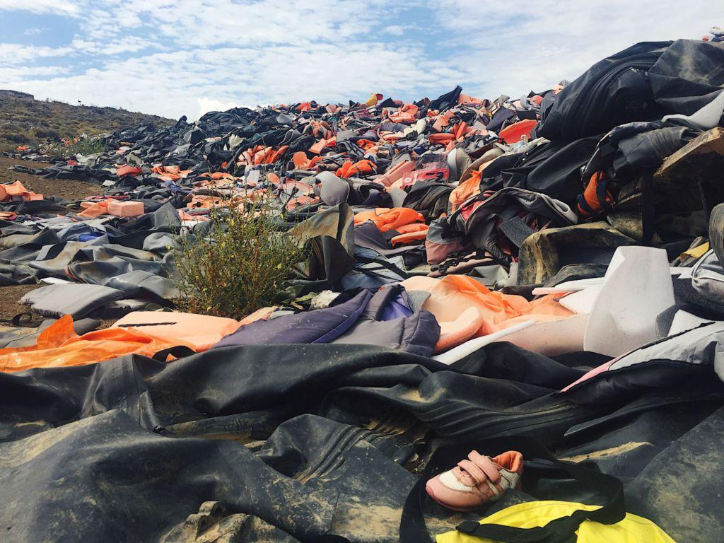 Disregarded+life+jackets+are+thrown+into+a+growing+heap+after+refugees+land+on+shore.