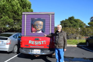 Posing next to his semi-famous Gandhi mobile, Jes Richardson, substitute teacher, is also a well known peace and human rights activist.