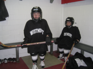 Suiting up to play, the Mandel boys prepare for their game in the locker room when they first began ice hockey.