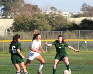 Maneuvering her way through the offenders , freshman Shannon Watridge runs for the ball.
