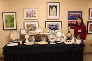 Geraldine Ganun standing next to her table full of handmade pottery.