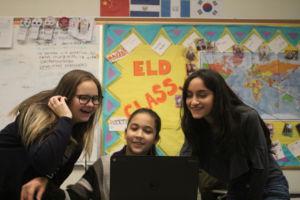 Rodriguez usando un Chrome Book para ayudar a un estudiante de segundo año