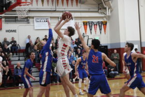 Junior Jack Gerson jumps to make a basket for the Giants at the boys' varsity basketball game against Tam on Tuesday.