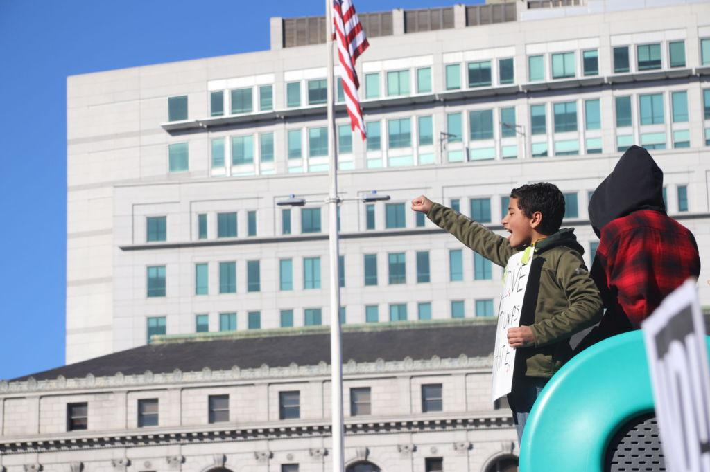 A young boy raises his fist in enthusiasm at Civic Center.