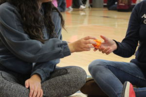 Passing a paper ball, students learn each others name through a group game.