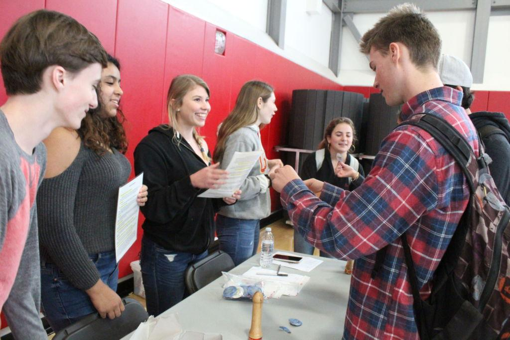 Senior Zach Tull listens in as Peer Resource students inform him on condoms.