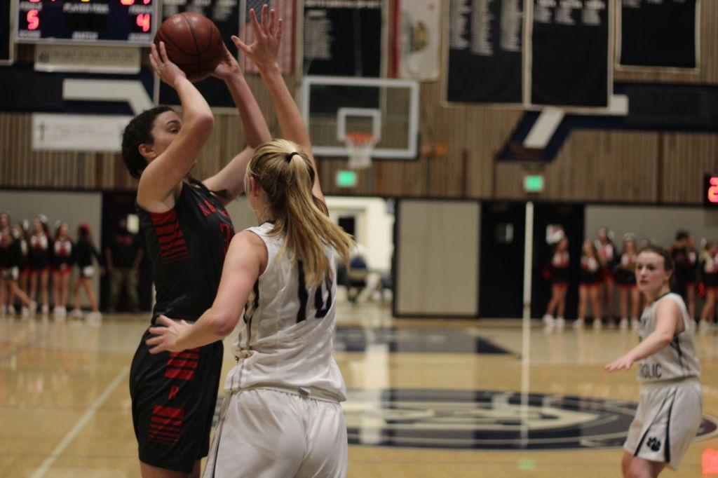 Julia Guisti rises and shoots over a MC defender