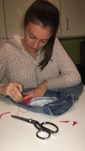 Sewing late in the night, senior Anna Martin works on detailing pants.