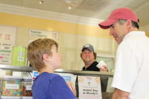Ordering ice cream, 1984 Redwood varsity swim team captain, Chuck Muller, and his son, Charlie Muller, debate over ice cream sizes to order.