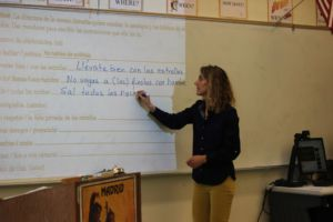 Writing on the board in Honors 7-8, Mrs. Phillips teaches her class about verb tense.