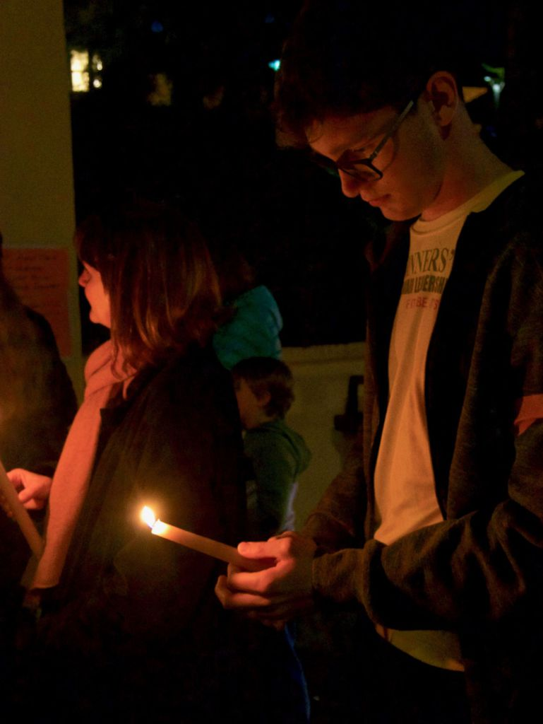 Holding a candle, a student listens to a speech made by a peer.