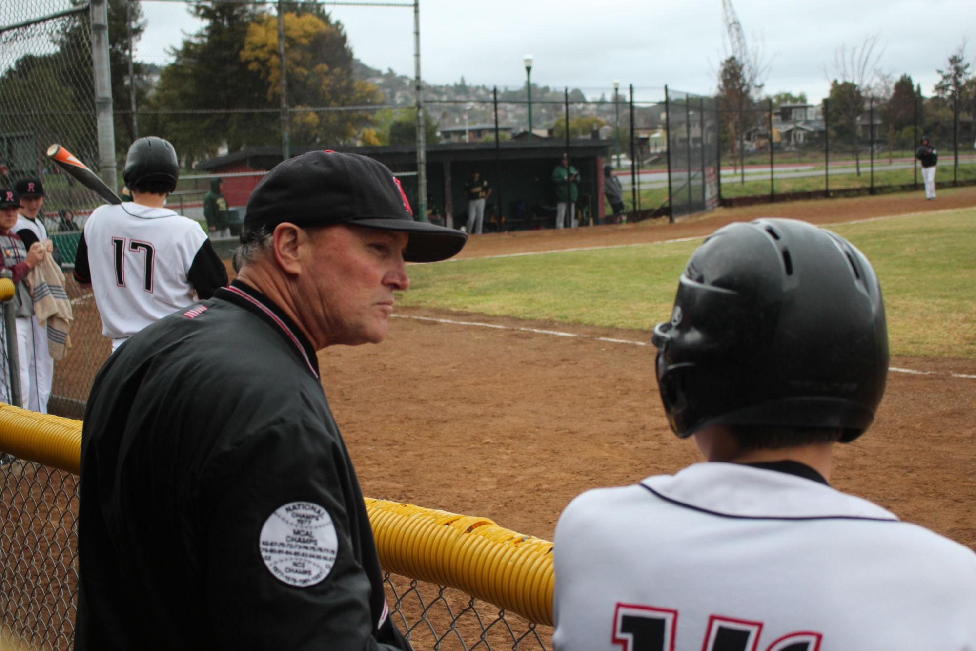 Standing+in+the+dugout%2C+assistant+coach+Dan+Watson+chats+with+Nathan+Hirsch.
