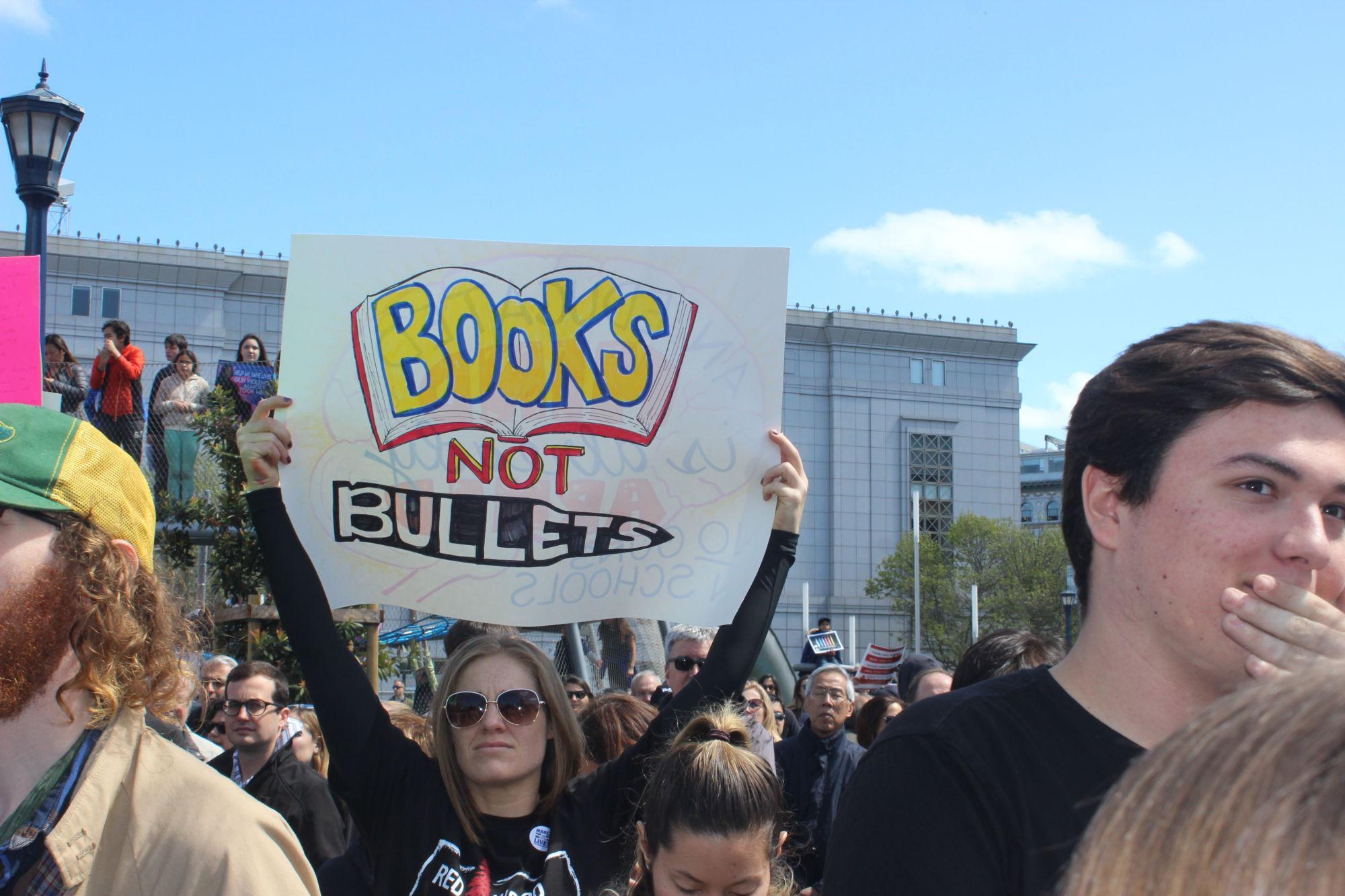 Teacher+Amy+Mastromonaco+holds+a+poster+that+reads+%E2%80%9CBooks+not+bullets%E2%80%9D