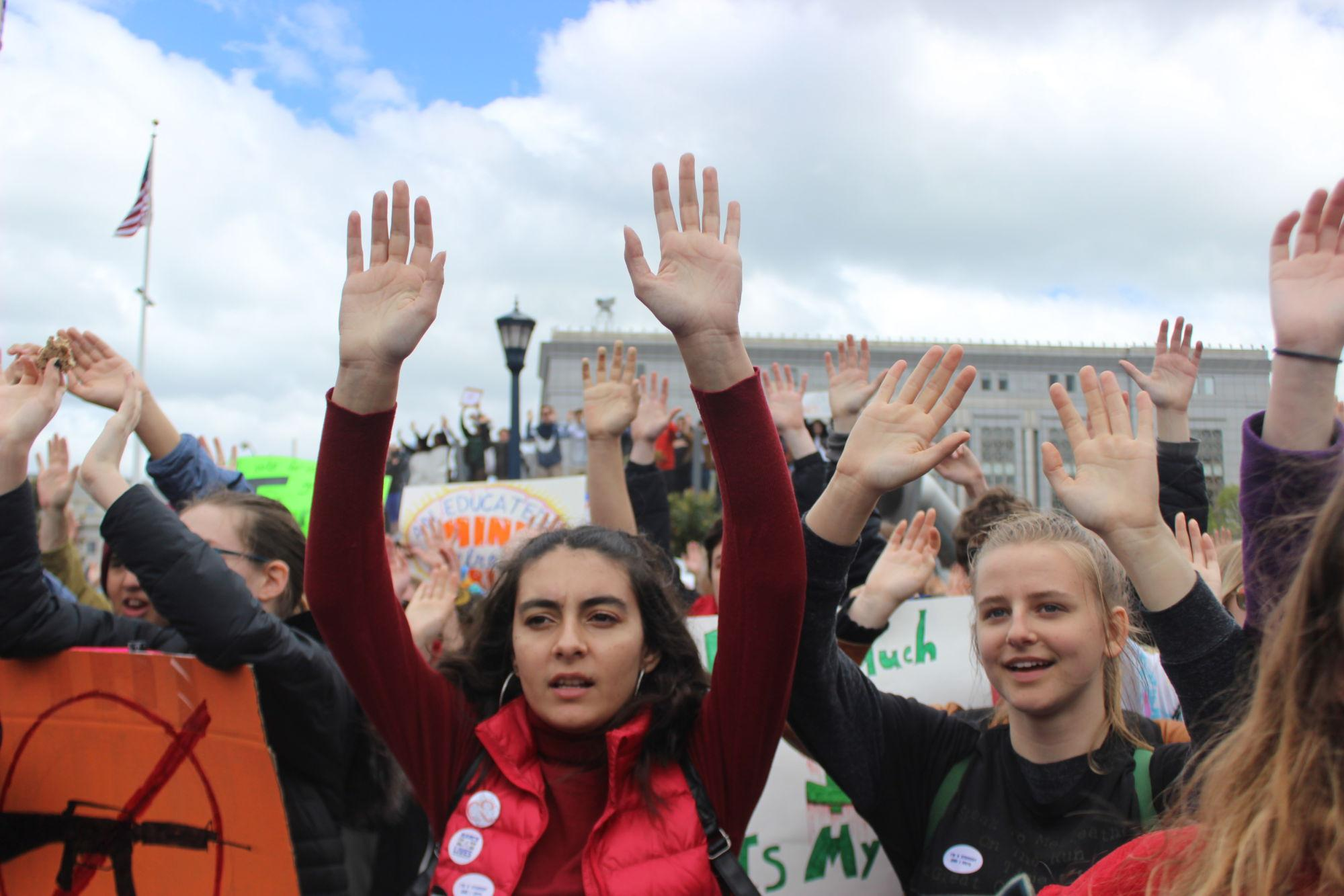 Students+including+sophomore+Maria+Saloom+and+senior+Emma+Ross+raise+arms+in+honor+of+the+all+those+who+have+lost+their+lives+due+to+unfair+gun+policies