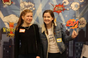 Sophomores Olivia Raskin and Claire Fogarty stand in front of a superhero backdrop before keynote speaker Pamela Hamamoto takes the stage