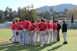 The varsity baseball team huddles up during practice discussing their previous game.