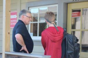 Principal Sondheim stands and talks to junior Sam Mayerhofer during the walkout.