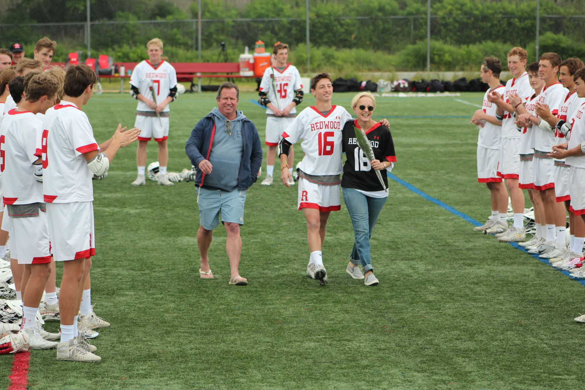 Reeser+walks+with+his+parents+to+celebrate+Senior+Day+before+the+game+begins