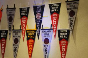 The walls, clad with pennants earned by athletes, exhibit the successes of various teams.