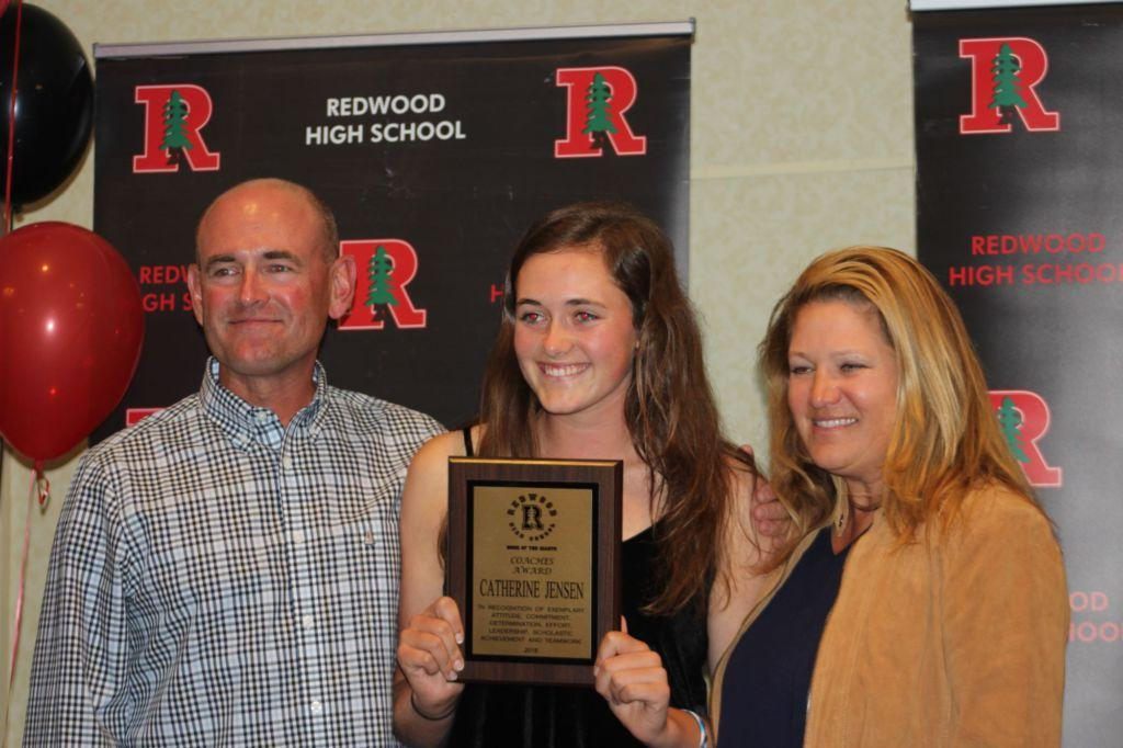Senior Catherine Jensen beams alongside her parents while holding up her coaches award.