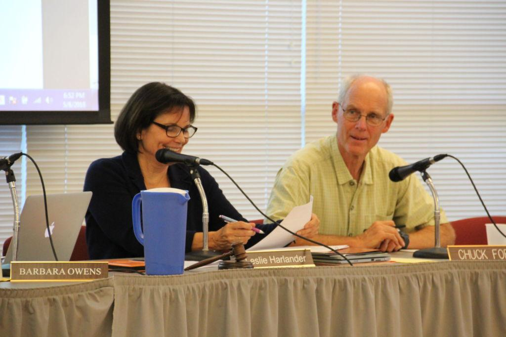 Board President Leslie Lundgren Harlander and board member Chuck Ford look over a resolution during the board meeting on May 8th.