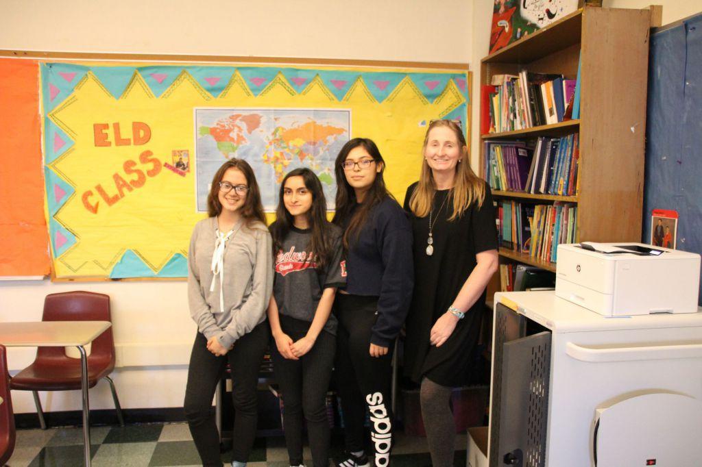 De pie con orgullo junto a la señal de la clase de ELD, (de la izquierda a la derecha) Madu Ferreira Vidal, la paraedúcadora de ELD Xenia Rodriguez, Maria Villar y la profesora de ELD, Debbie McCrea, están entusiasmadas por otro día de clase.