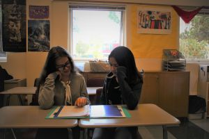 Poring over notes in their binder, Madu Ferreira Vidal and Ruth De Britto help each other study.