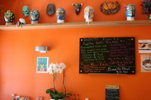 Display of vibrant orange walls where traditional masks from Mexico hang