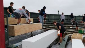 Nordstrom and his friends paint wood boxes on the bleachers to revamp Endriss field
