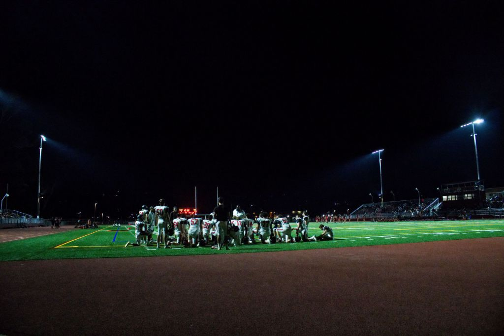 The stadium lights shine down onto the Redwood Giants during their halftime talk