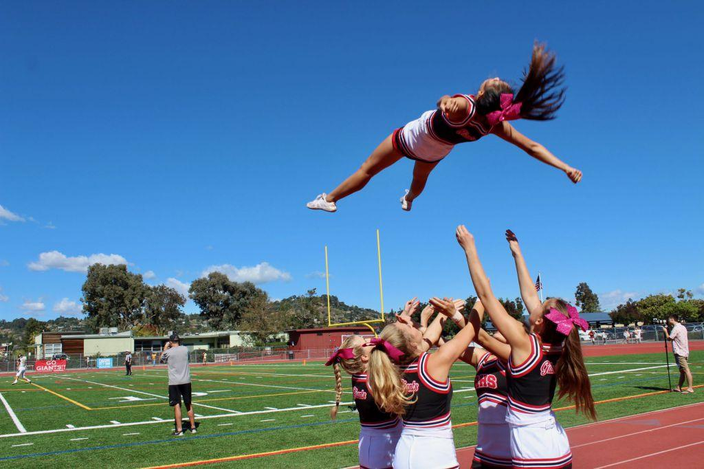 Cheerleaders+practice+stunts+on+the+sideline.