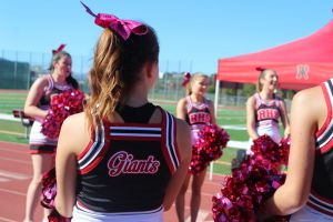 Cheerleaders support the football team in uniforms they fundraised for themselves.